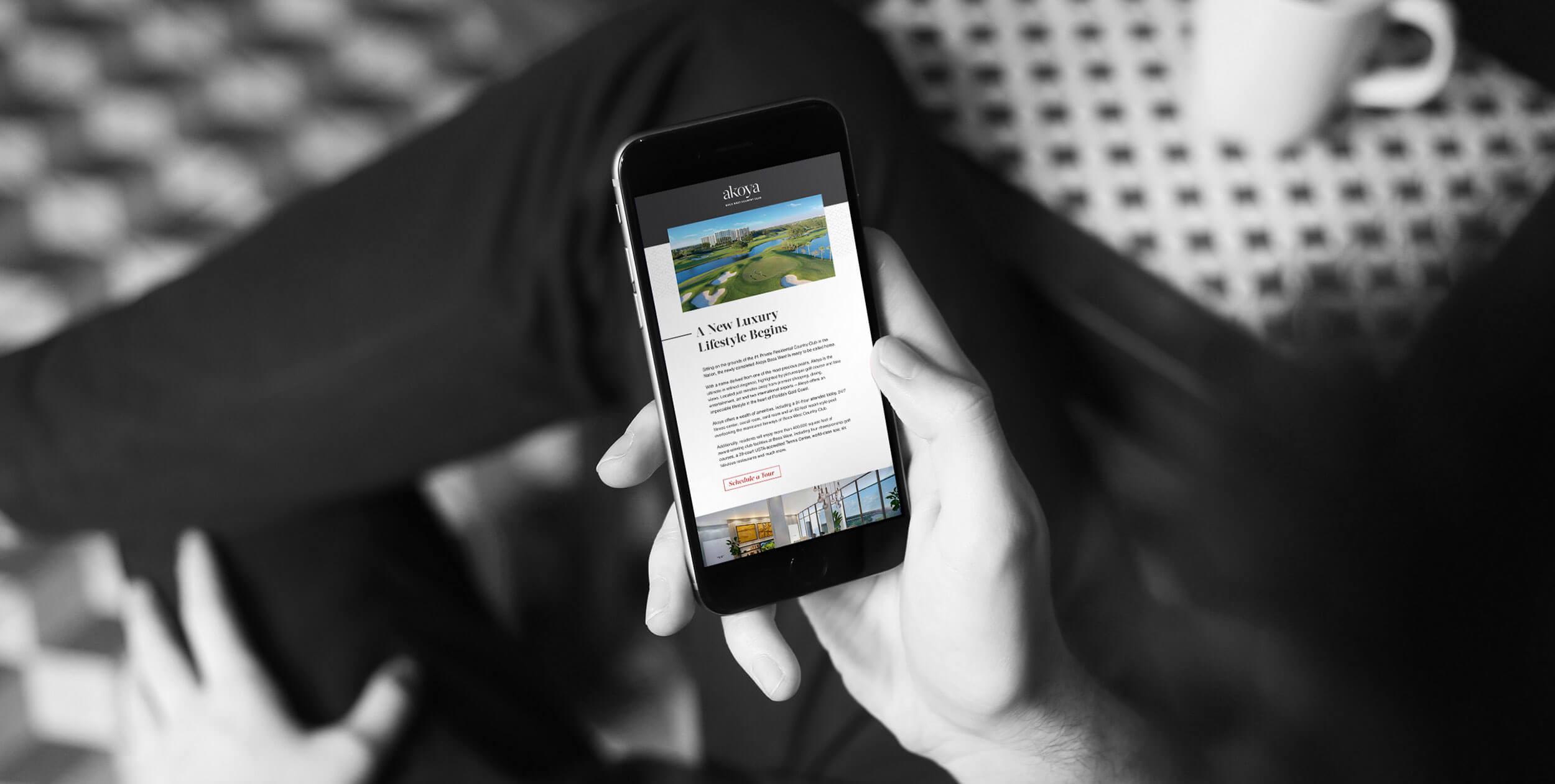 Man holding phone viewing Akoya website